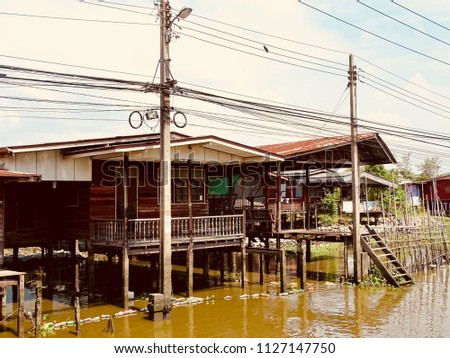 Landscape view of Countryside houses at the riverside. City dwellers live along canals in Asia. Picture of the peaceful village along the canal. #1127147750