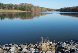 Landscape view of lake in Seneca State Park Maryland United States on autumn afternoon with reflections in water and white grass in foreground