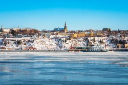 Landscape view of Levis City on south shore of St Lawrence river by ferry boat crossing connects Quebec city and Levis, Canada. Beautiful winter cityscape with snow covered buildings, trees and river.