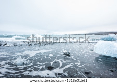 Stock Photo Landscape view of many blue glacier icebergs in Jokulsaron lagoon lake diamond beach in Iceland with black sand and waves shore water