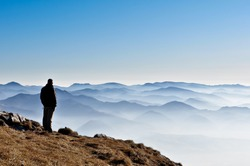 Landscape view of misty autumn mountain hills and man silhouette