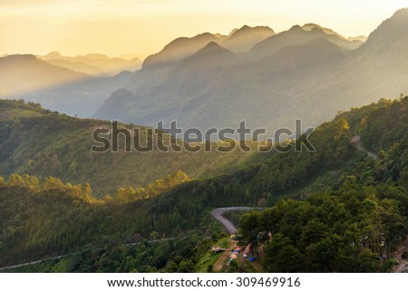 landscape view of mountain , tent , road in forest with sunset scene
