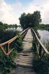 Landscape view of Old small wooden bridge across the lake. Fishman house on an island surrounded by wather and forest