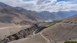Landscape view of Pamir river gorge in high altitude desert bordering Afghanistan with Hindu Kuch mountain range in background, Wakhan Corridor, Gorno-Badakshan, Tajikistan