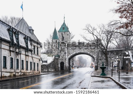 Landscape view of Porte Saint Louis gate on the fortified wall with street during blizzard in winter season, fortifications of Quebec national historic site, historical landmark in Quebec City, Canada