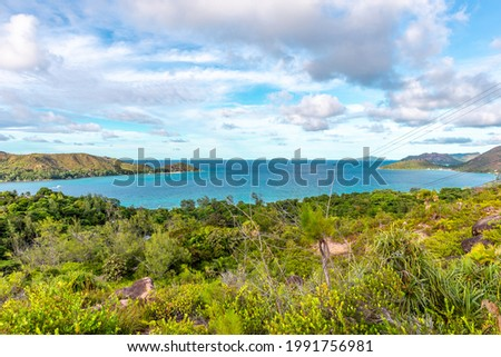 Landscape view of Praslin Island, Seychelles, seen from Zimbabwe Point (Grand Fond), with lush tropical vegetation and turquoise water overlooking Praslin coastline with Curieuse Island. Stock photo ©