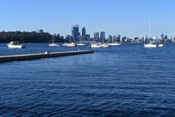 Landscape view of sail boats mooring in Matilda Bay on Swan River against Perth financial district  skyline in Western Australia.