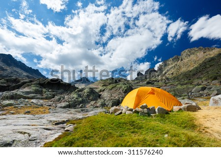 Landscape View of the Glacial Cirque of the Sierra de Gredos Regional Park with the Almazor Peak in the Background and an Orange Camping Shelter Tent in the Foreground, Avila, Castilla y Leon, Spain #311576240