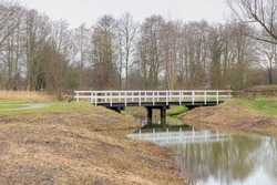 Landscape view of white wooden bridge crossing canal with reflection on the water, Typical netherlands nature with small canal or ditch in the forest or park, Winter cold day with cloudy sky.