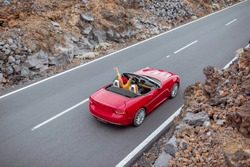 Landscape view on the beautiful straight road on the volcanic valley with woman driving a red cabriolet, view from above. Traveling by car on Tenerife island, Spain