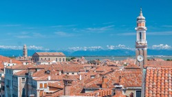 Landscape view over the red roofs of Venice timelapse, Italy seen from the Fundaco dei Tedeschi. Bell tower. Blue cloudy sky at summer day