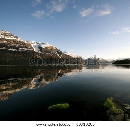 Landscape with a fjord, mountains whose peaks are covered with snow and a bright blue sky, taken in Norway