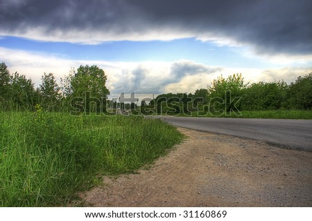 Landscape with a green grass and the asphalted road, on thunder-storm eve