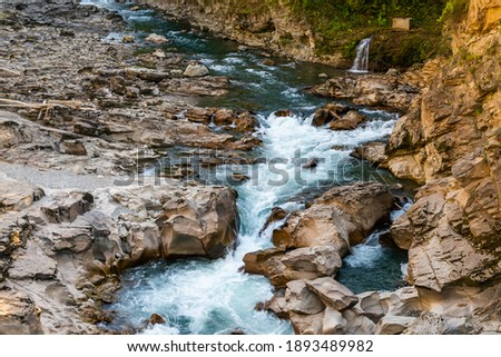 Landscape with a mountain river flowing through canyon.