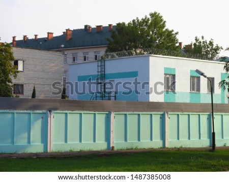 Landscape with a prison behind a fence and barbed wire. Correctional colony of strict regime #1487385008