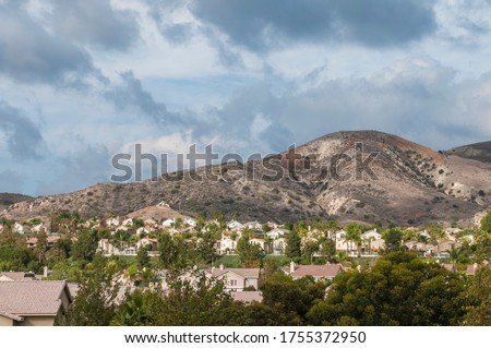 Landscape with a residential zone at the foot of the mountain under a beautiful cloudy sky, near the city of Rancho Santa Margarita, Orange County California USA. Сток-фото ©