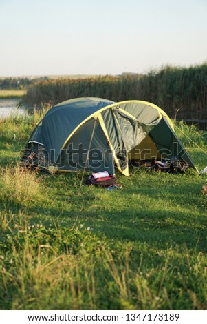 Landscape with a tent with a beautiful view near the river. Spring summer outdoor recreation. Stock background, photo #1347173189