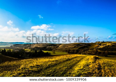 Landscape with a working wind turbines in field . Concept of ecological lifestyle. - Shutterstock ID 1009339906
