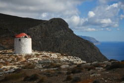 Landscape with an old traditional stone windmill with a red rooftop overlooking the South Aegean Sea in Amorgos island, Cyclades Greece.