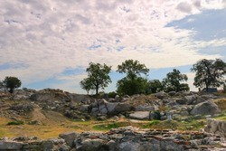 landscape with an uneven rocky surface with trees, stones, dry grass and a blue sky with clouds in the background - Roman ruins on Nevet Tepe hill in Plovdiv, Bulgaria