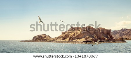 Landscape with ancient Citadel of Saladin on the Farun Island in the Gulf of Aqaba and flying seagulls over the Red Sea. Old fortress of Sultan Salah El Din in Taba, travel on Sinai Peninsula. Stock fotó ©
