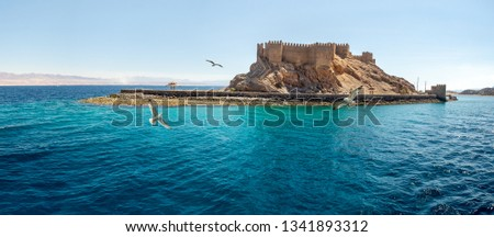 Landscape with ancient Fortress of Saladin on the Pharaoh Island in the Gulf of Aqaba and flying seagulls over the Red Sea. Old Castle of Sultan Salah El Din in Taba, travel on Sinai Peninsula. Stock fotó ©
