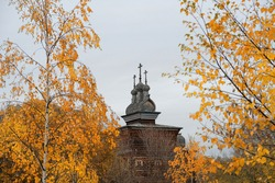 landscape with autumnal trees and Church. Orthodox wooden Church and yellow birch leaves. fall season. Russia, Moscow, park Kolomenskoye.