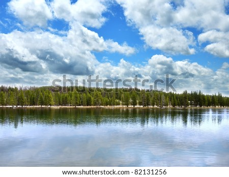 landscape with big lake with forest in high mountains  and beautiful sky