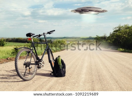Landscape with bike on the road and UFO. Abduction of people by aliens. Fiction scene with alien spaceship. Photo with 3d rendering element