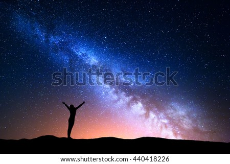Landscape with blue Milky Way and yellow light. Colorful night sky with stars and silhouette of a standing sporty girl with raised-up arms on the hill on the background of beautiful universe.