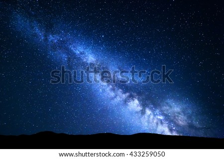 Stock Photo Landscape with blue Milky Way. Night sky with stars and hills at summer. Beautiful universe. Amazing universe. Space background. Beautiful galaxy