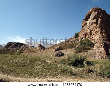 Landscape with blue sky, rock formations (some interesting) and soil with some grass and cattle trail. Taken on the way to Fann mountains (Pamir, Tajikistan) in Central Asia.