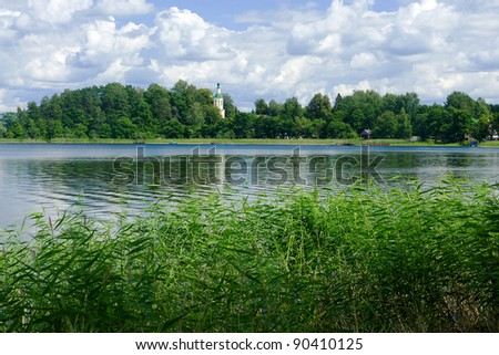 Landscape with church, grass, trees, reflecting in water surface of lake
