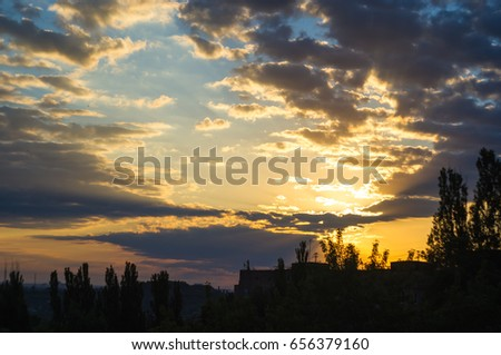 landscape with dramatic light - orange clouds and the outline of trees at sunrise #656379160