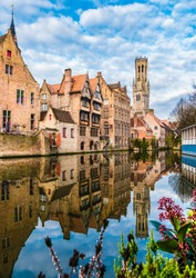 Landscape with famous Belfry tower and medieval buildings along a canal in Bruges, Belgium