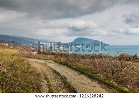 Landscape with gray sky, Ayu-Dag mountain and rural road through the vineyards in Crimea