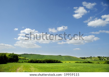 Landscape with green fields, blue and cloudy sky.