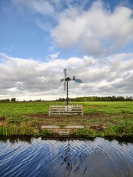 Landscape with green meadows and windmill in Zaans Rietveld for the discharge of water from the nature reserve to the drainage water against a background of blue sky with scattered clouds