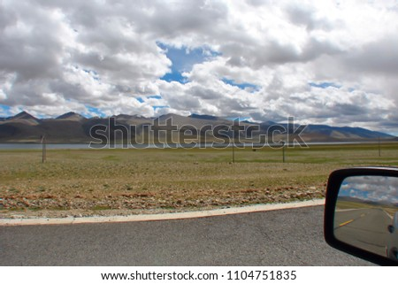 landscape with highway along the river and mountain range in the highlands, picture of the road and white clouds reflected in the car's side mirror, picture in picture, Tibet