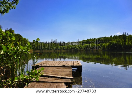 Landscape with lake, forest, and blue sky