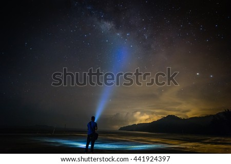 Landscape with Milky Way. Night sky with stars and silhouette of a standing happy man on the beach with the torchlight