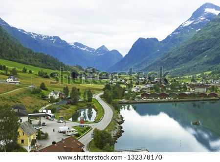 Landscape with mountains and rural houses in village Olden in Norwegian fjords.