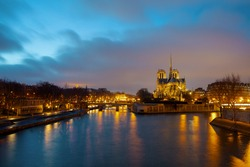landscape with notre dame de paris and Seine river in Paris, France at night in the evening.