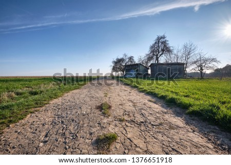 Landscape with old and decaying gravel road with some old huts and bare trees as well as green grass and meadows. Near Tauchersreuth, March 2019 #1376651918