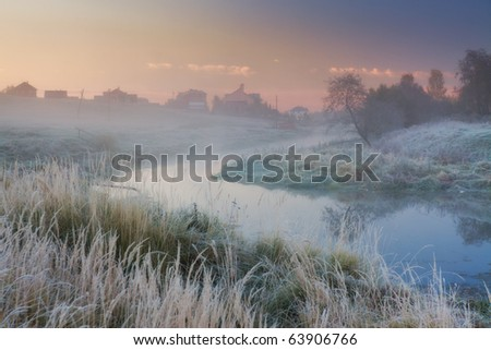 Landscape with river and frozen grass at misty sunny morning
