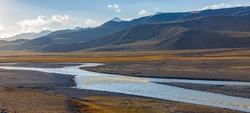 Landscape with road on wide floodplain of  mountain river. Panorama with  road along the riverbed and mountain steppes at an altitude of more than 3000 meters in autumn in Asia.