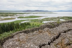 Landscape with rocks, Oxara river and large Thingvallavatn lake in Thingvellir, Iceland in overcast weather