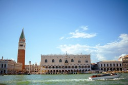 landscape with saint marks campanile, doges palace, motorboat and grand canal in Venice, Italy.
