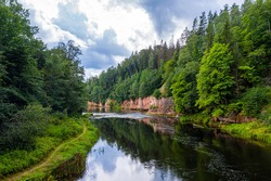 landscape with sandstone cliffs on the Gauja river bank, fast flowing and clear river water, Kuku cliffs, Gauja National Park, Latvia