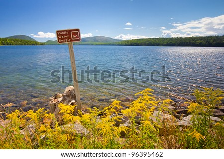 Landscape with sign prohibiting swimming in public water supply reservoir